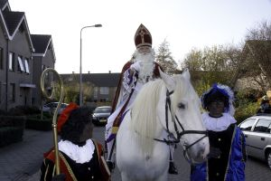Sinterklaas on his white horse, accompanied by two Black Petes \br (Flickr Creative Commons)