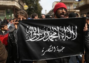 Credits: The Japan Times Protestors demonstrate against Bashar Al-Assad while holding Al-Nusra flags