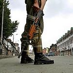Soldier holds gun in Kashmir.