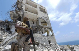 A Saudi soldier stands next to a bombed out building in the port city of Aden in September of 2015. https://flic.kr/p/Gxzq45